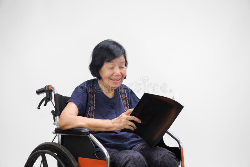 Senior asian woman smiling while reading magazine stock image