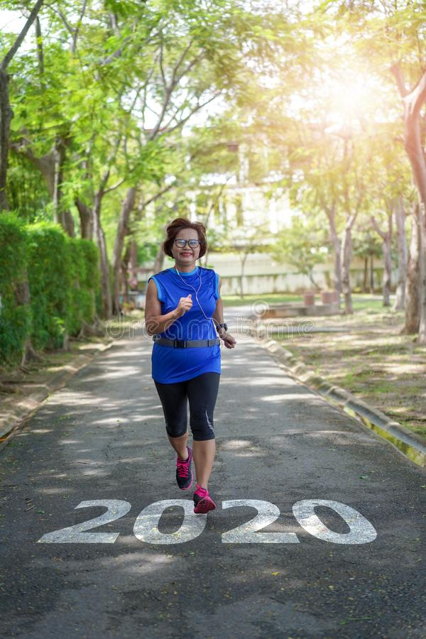 Senior asian woman start to new year 2020 plans goals happy jogging running in the park royalty free stock photos