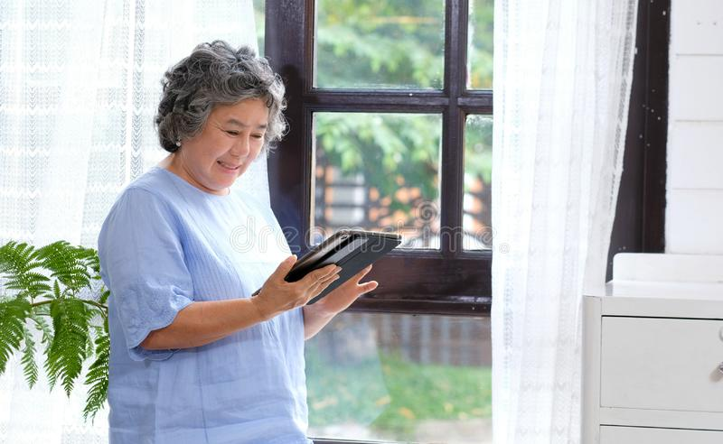 Senior asian woman using digital tablet computer at home background, Retirement asian woman and digital tablet standing by home royalty free stock images