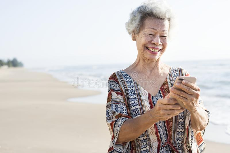 Senior Asian woman using a phone at the beach stock images