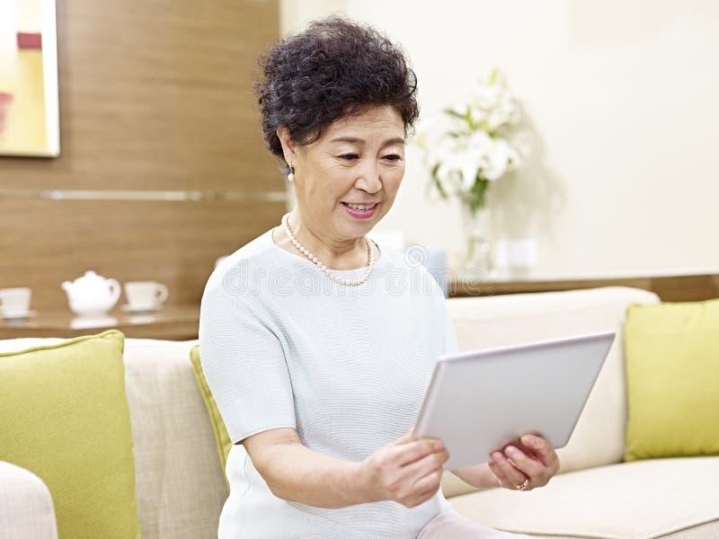 Senior asian woman using tablet computer royalty free stock photos