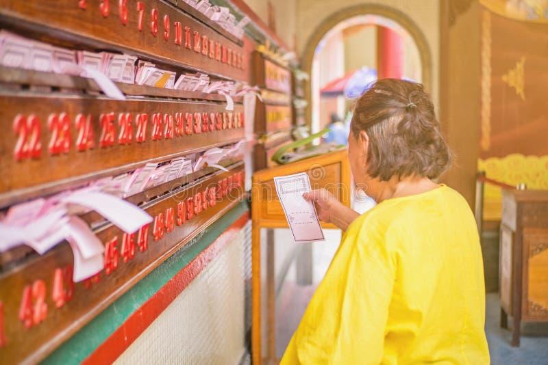 Senior Asian women Pick up Chinese daily fortune teller paper in  Wat Mangkon Kamalawat temple in bangkok. Senior Asian woman Pick up Chinese daily fortune stock image