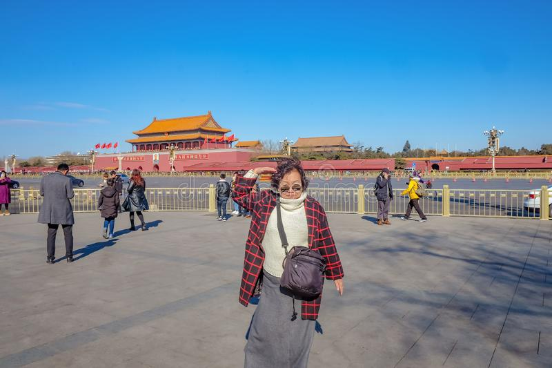 Senior asian women traveler try to make Salute pose and stand on Tiananmen square in front of the Forbidden Palace. Beijing/China - 25 February 2017: Senior royalty free stock photos