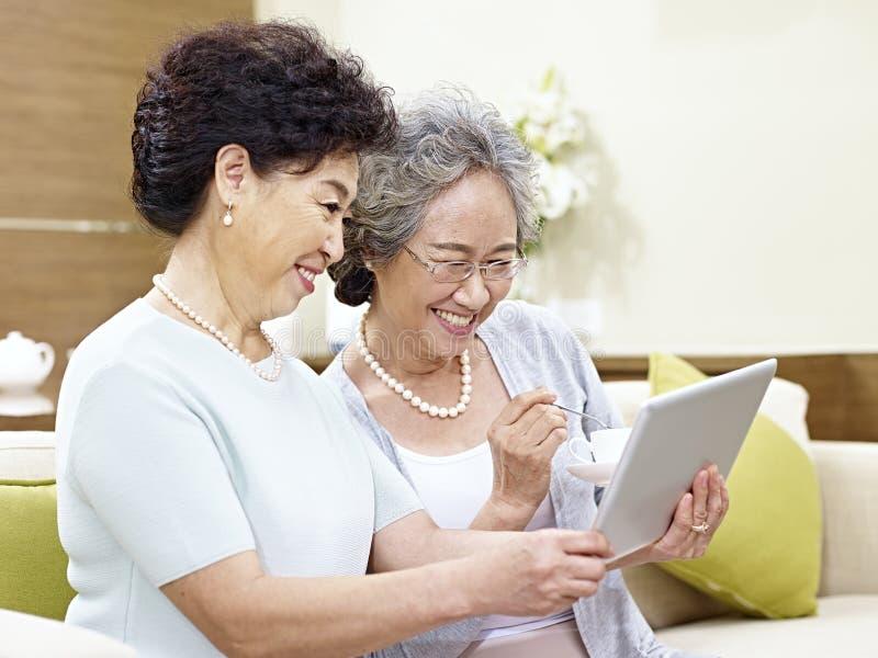 Senior asian women using tablet computer stock image
