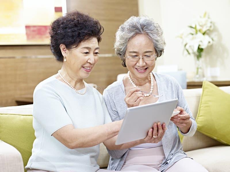 Senior asian women using tablet computer royalty free stock photo