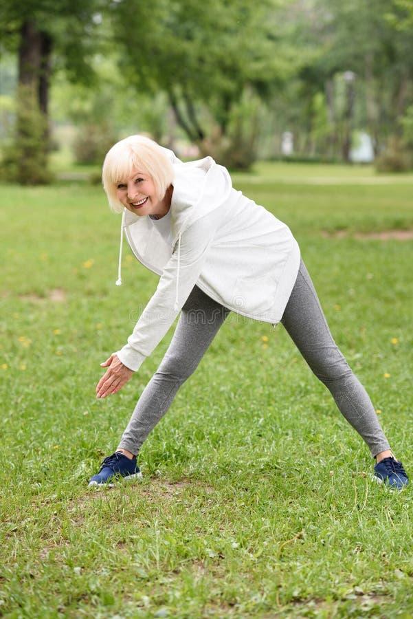 senior athletic woman in sportswear training on green lawn royalty free stock photo