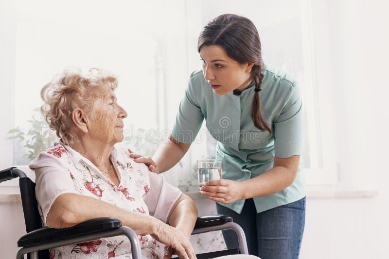 Senior auf Rollstuhl, Unterstützungskrankenschwester, die ihr Glas Wasser gibt stockfotos