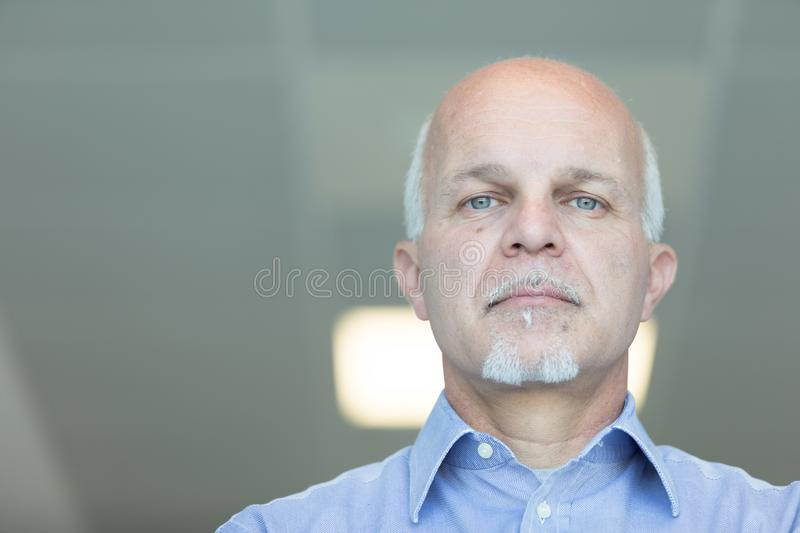 Senior balding man with a deadpan expression. Senior balding man with blue eyes and a deadpan expression staring down at the camera in a low angle head portrait royalty free stock photos