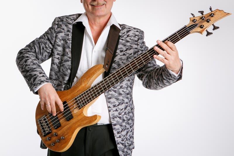 Senior bawić się basową gitarę odizolowywającą na białym tle zdjęcie stock