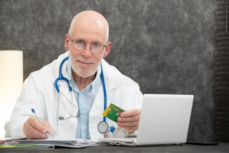 Senior bearded doctor with health insurance card royalty free stock photography
