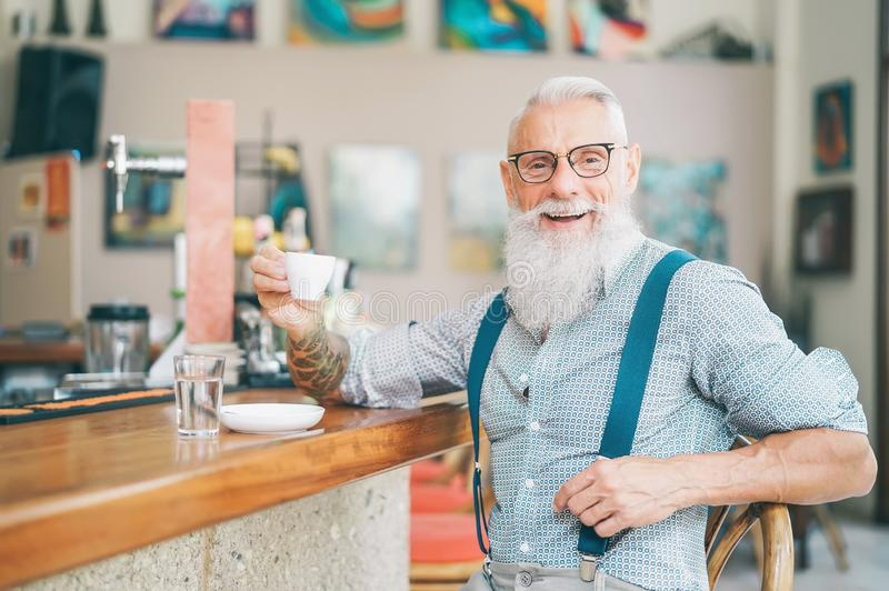 Senior bearded man drinking coffee sitting bar counter - Happy mature male having fun enjoying time outdoor stock image