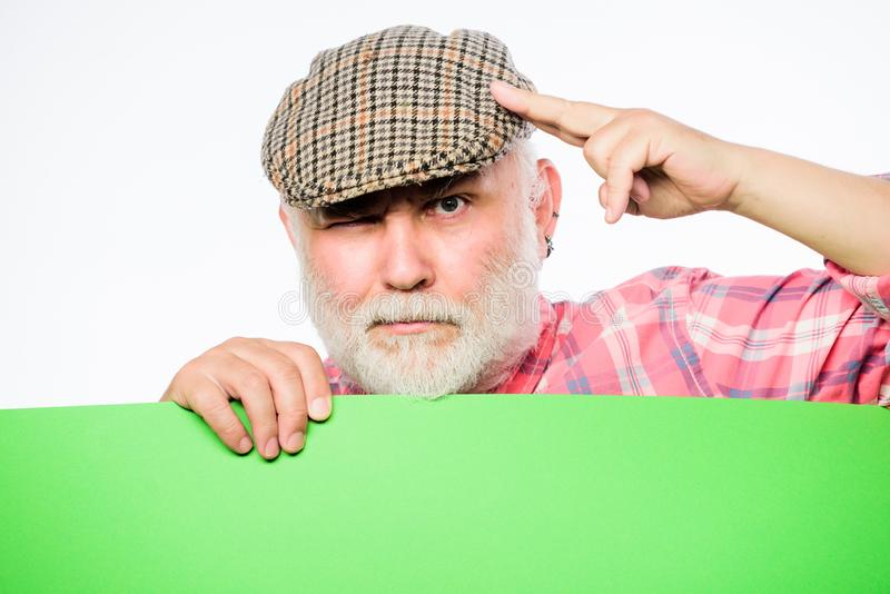 Senior bearded man peek out of banner place announcement. Pensioner grandfather in vintage hat hold poster information stock photography