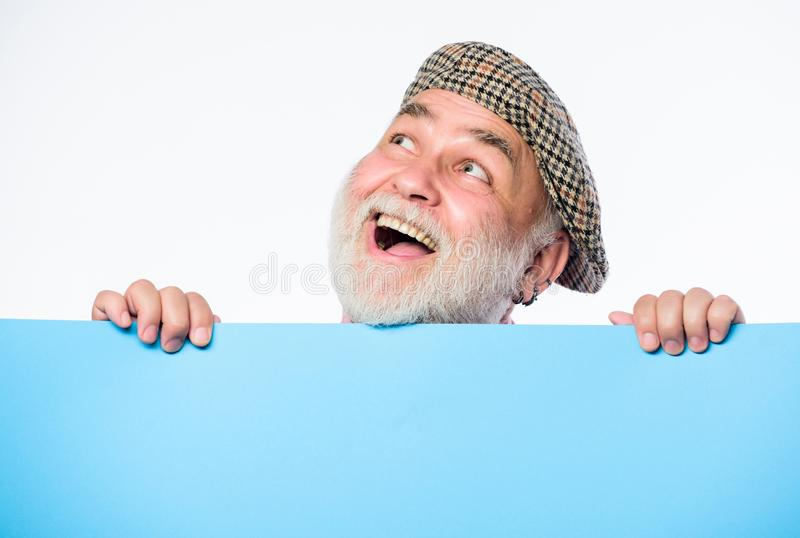 Senior bearded man peek out of banner place information. Advertisement elderly people. Charming pensioner in vintage hat stock photo