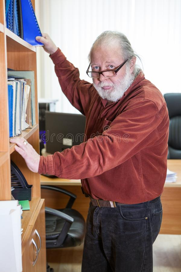 Senior bearded man puts a document into a shelf in office. Brown shirt and eyeglasses royalty free stock images