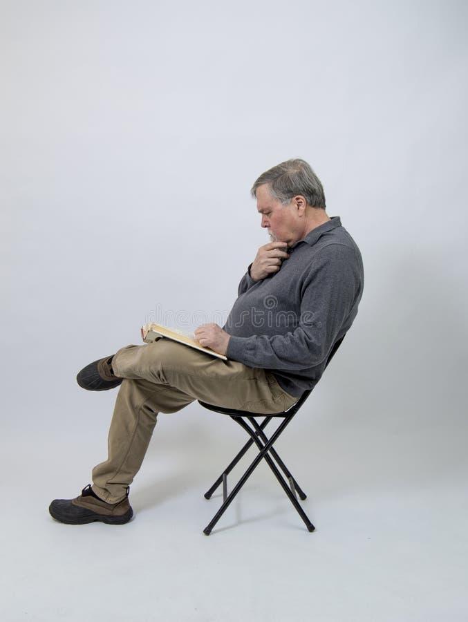 Senior bearded man reading isolated on white royalty free stock photography