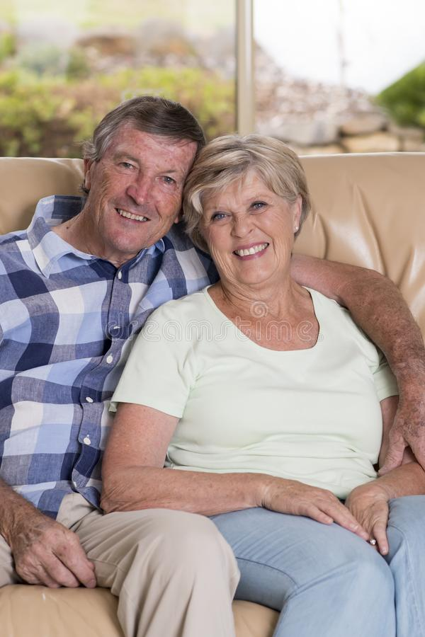 Senior beautiful middle age couple around 70 years old smiling happy together at home living room sofa couch looking sweet in life. Time husband and wife royalty free stock photos