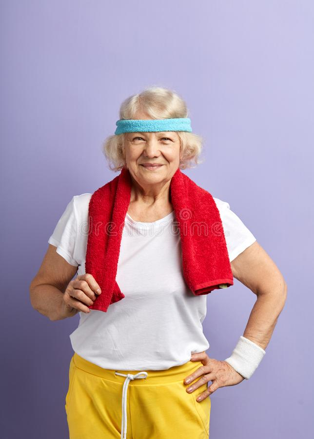 Elderly sportswoman with headband and red towel on neck, looking at camera royalty free stock image