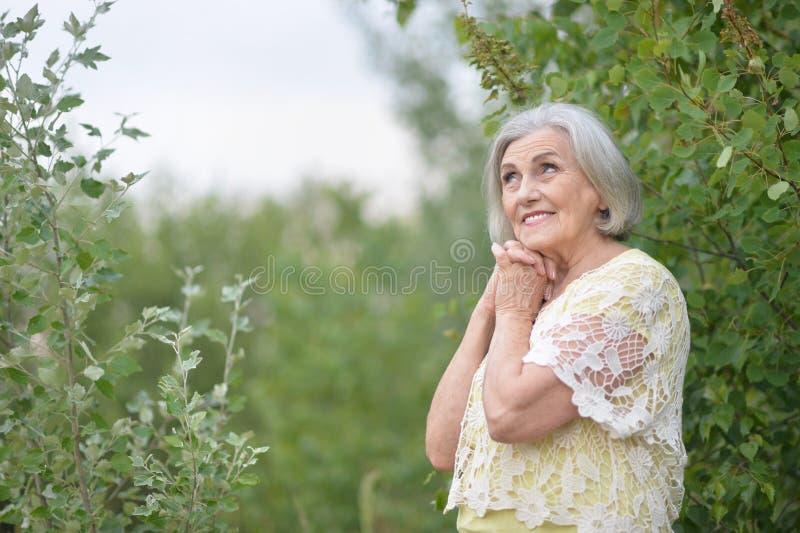 Portrait of senior beautiful woman in spring park. Senior beautiful woman posing in spring park royalty free stock photo