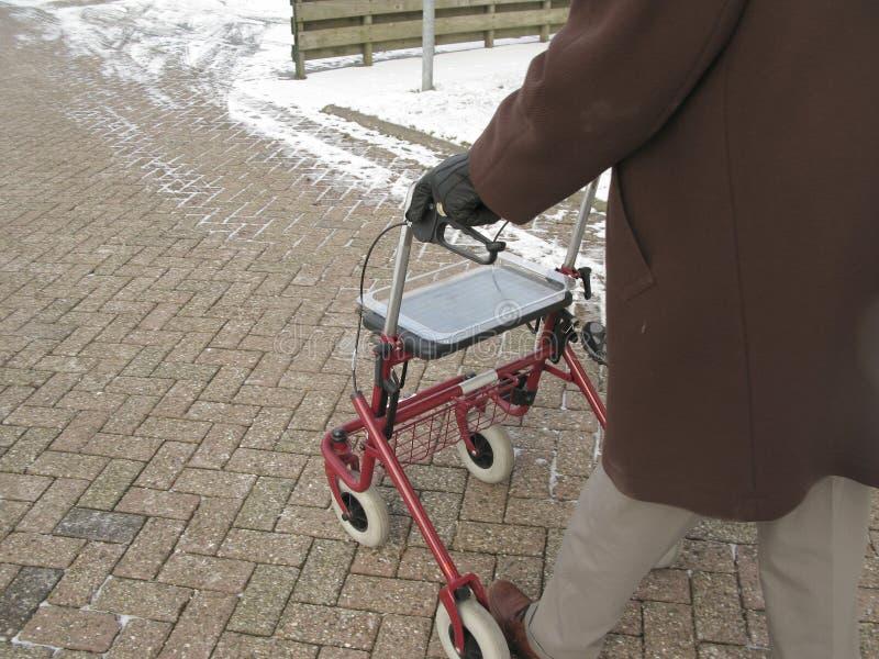 Senior behind wheeled walker in snow. Senior male walking behind wheeled walker in snow royalty free stock photos