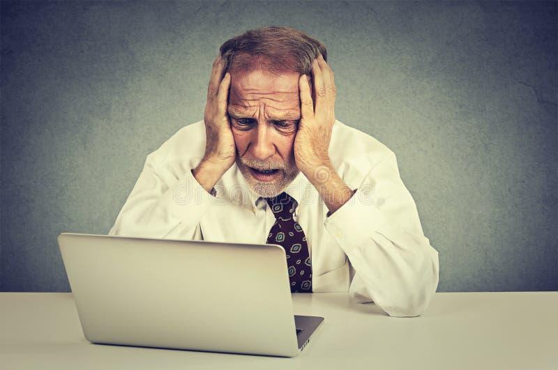 Senior betonte den Mann, der an dem Laptop arbeitet, der bei Tisch sitzt stockbild