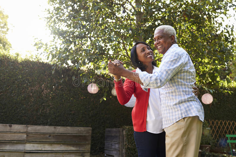 Senior black couple dancing in their back garden stock image