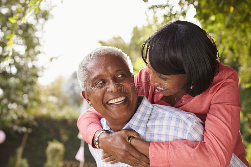 Senior black couple piggyback, looking at each other royalty free stock images