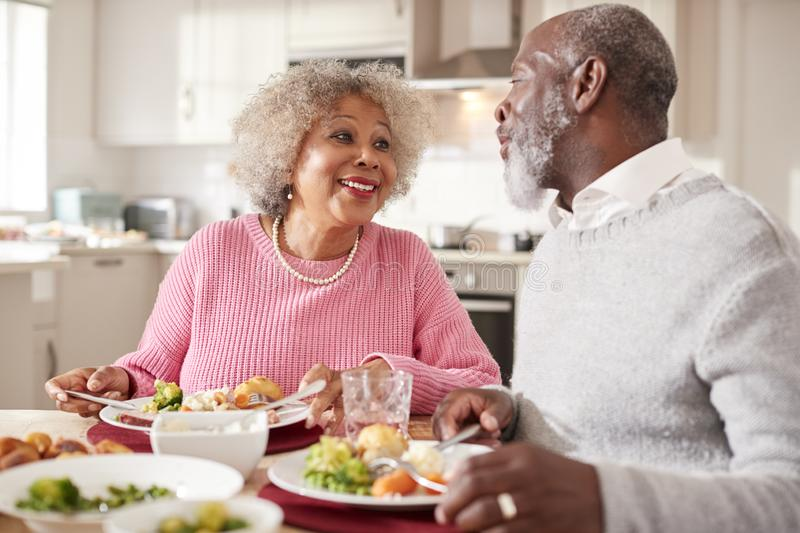 Senior black couple smiling to each other as they eat Sunday dinner together at home, close up royalty free stock photography
