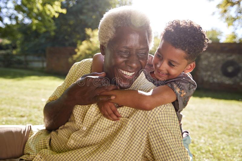 Senior black man sitting on grass, embraced by his grandson stock photography