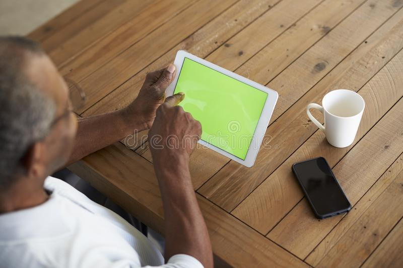 Senior African American  man sitting at table using tablet computer, elevated over shoulder view. Senior black man sitting at table using tablet computer stock images