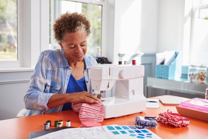 Senior black woman stitching fabric using a sewing machine stock images