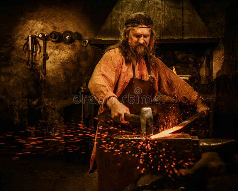 Senior blacksmith forging the molten metal on the anvil in smithy.  royalty free stock images