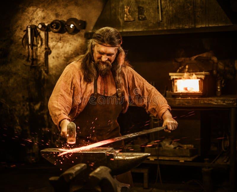 Senior blacksmith forging the molten metal on the anvil in smithy.  stock image