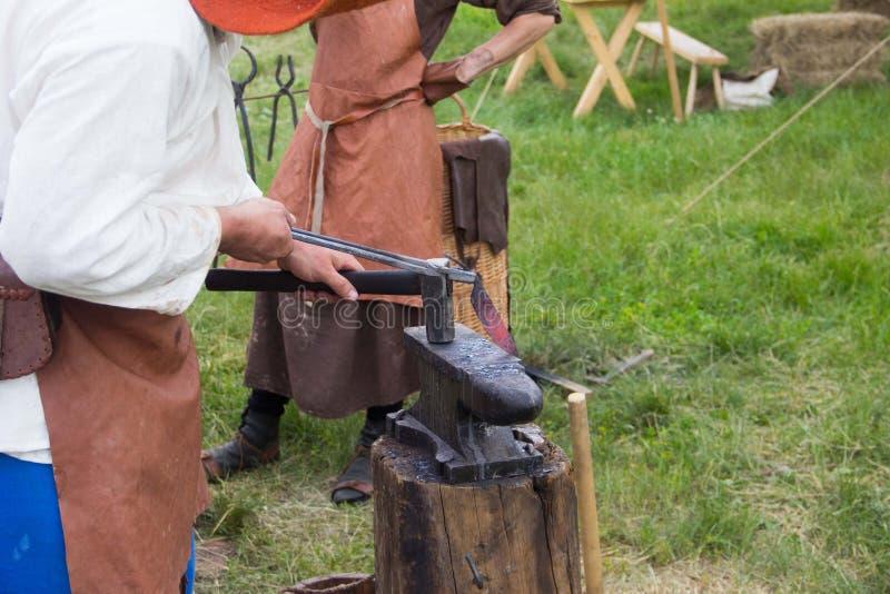 Senior blacksmith forging the molten metal on the anvil in smithy. Blacksmithing. Hammer and anvil. Blacksmith forging iron royalty free stock images