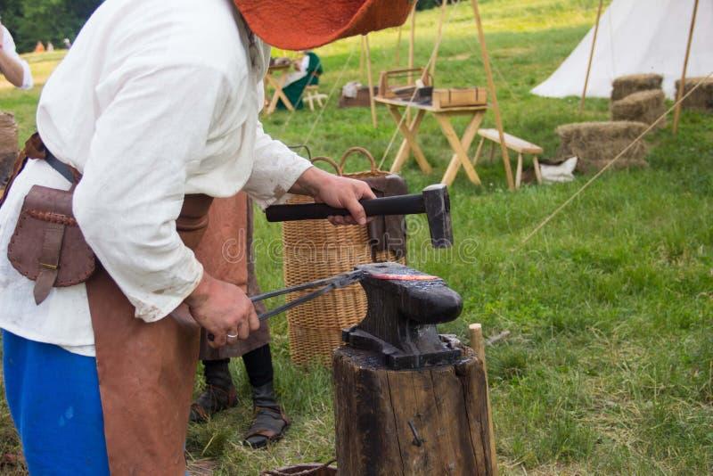 Senior blacksmith forging the molten metal on the anvil in smithy. Blacksmithing. Hammer and anvil. Blacksmith forging iron royalty free stock photography