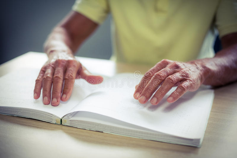 Senior blind man reading a braille book. At home royalty free stock photography