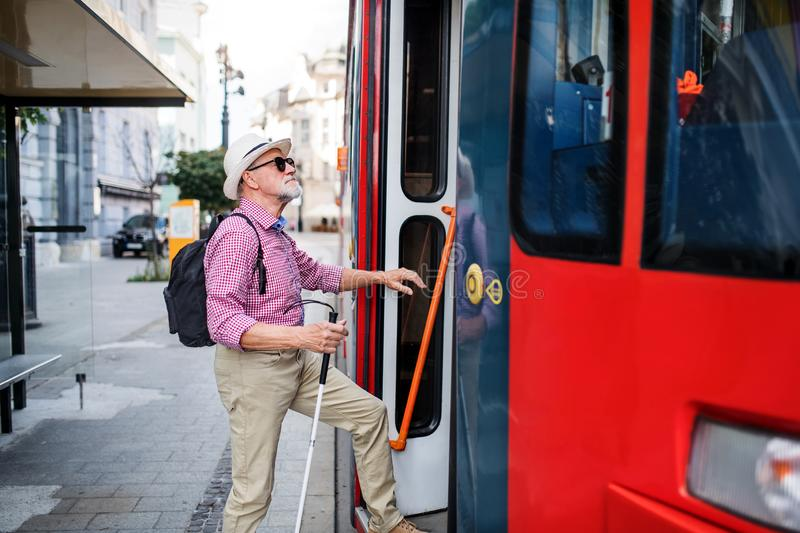 Senior blind man with white cane getting on public transport in city. stock photos