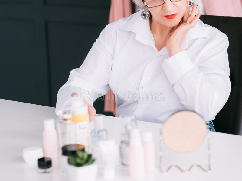 Senior blogger skin care products retailer woman. Successful senior blogger. Skin care products retailer. Elderly woman with beauty cosmetics around stock image