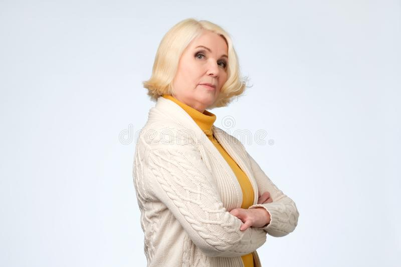 Senior blond woman looking with proud and arrogant emotions. She is proud of herself stock image