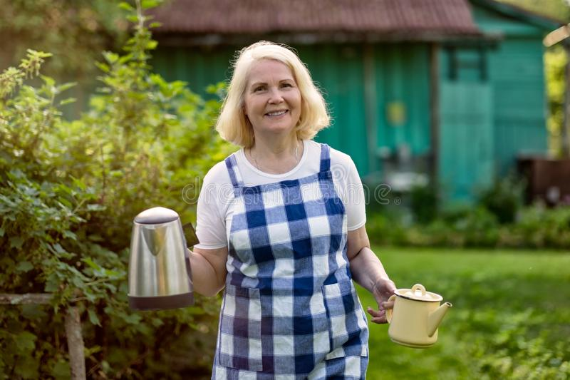 Senior blonde beautiful woman going with teapot to her guests at her farm stock photos
