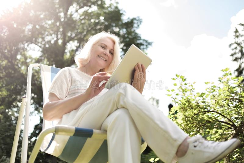 Senior blonde woman sitting in chair and using digital tablet in garden royalty free stock images