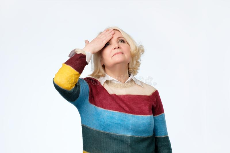 Senior blonde woman surprised with hand on head for mistake, remember error stock image