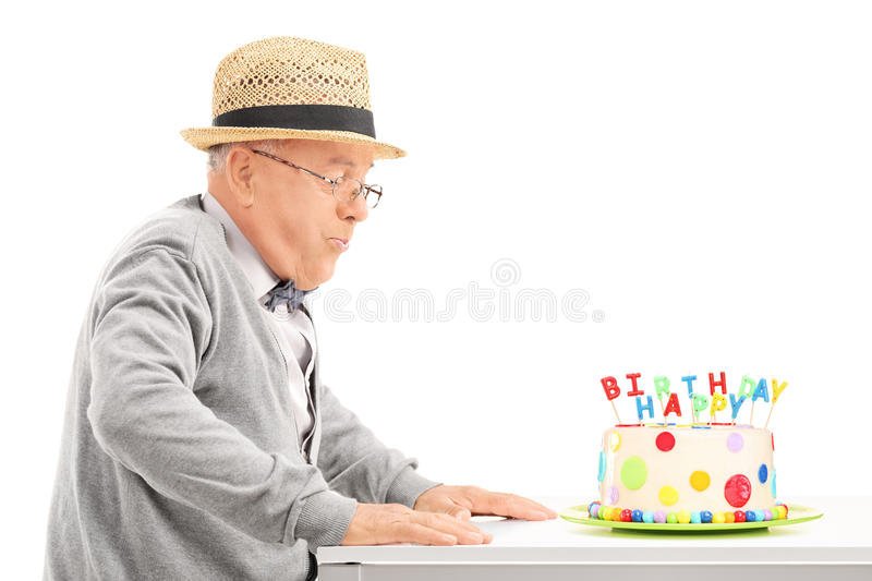 Senior blowing candles on his birthday cake. Isolated on white background royalty free stock photos