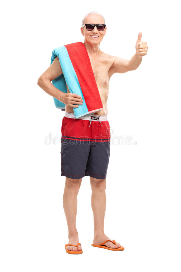 Senior in blue swim trunks giving a thumb up. Full length portrait of a senior in blue swim trunks carrying a towel over his shoulder and giving a thumb up royalty free stock photos
