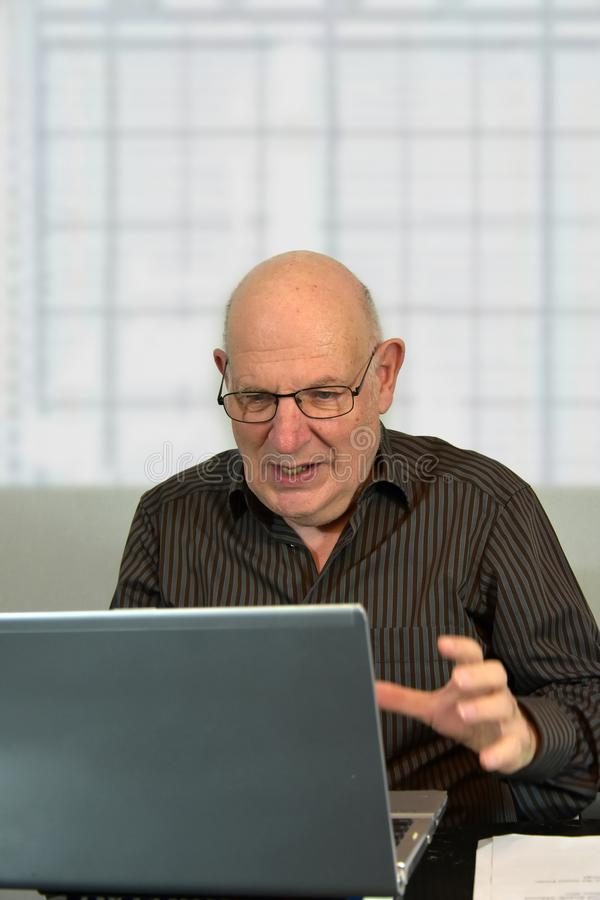 Senior boss works in his office and looks horrified at his comp. Senior boss casually dressed works in his office. He is appalled by what he sees on the computer royalty free stock images