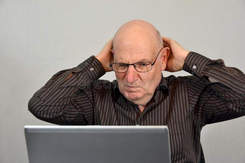 Senior boss works in his office and looks horrified at his comp. Senior boss casually dressed works in his office. He is appalled by what he sees on the computer stock photos