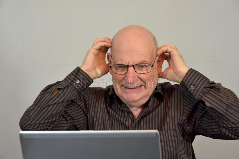 Senior boss works in his office and looks horrified at his comp. Senior boss casually dressed works in his office. He is appalled by what he sees on the computer royalty free stock photos