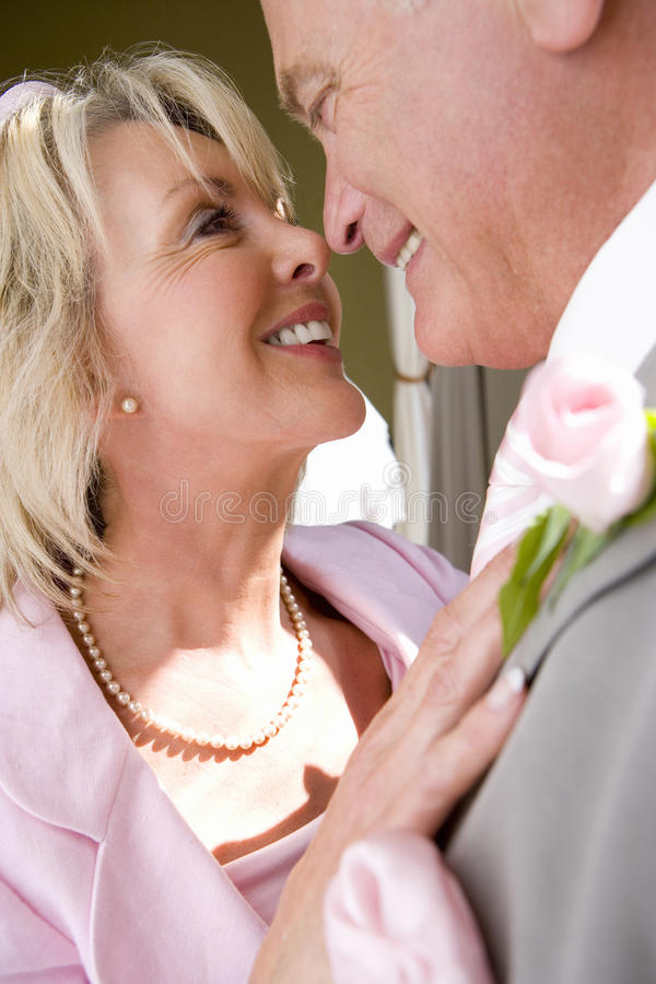Senior bride and groom preparing to kiss, close-up, side view stock image