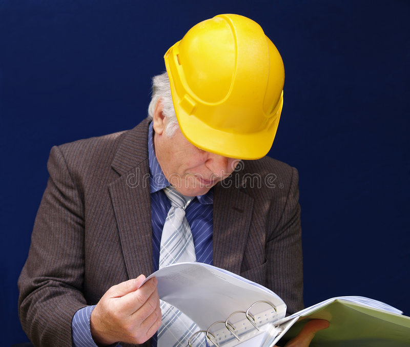 Senior builder. Checking his folder very carefully stock photos