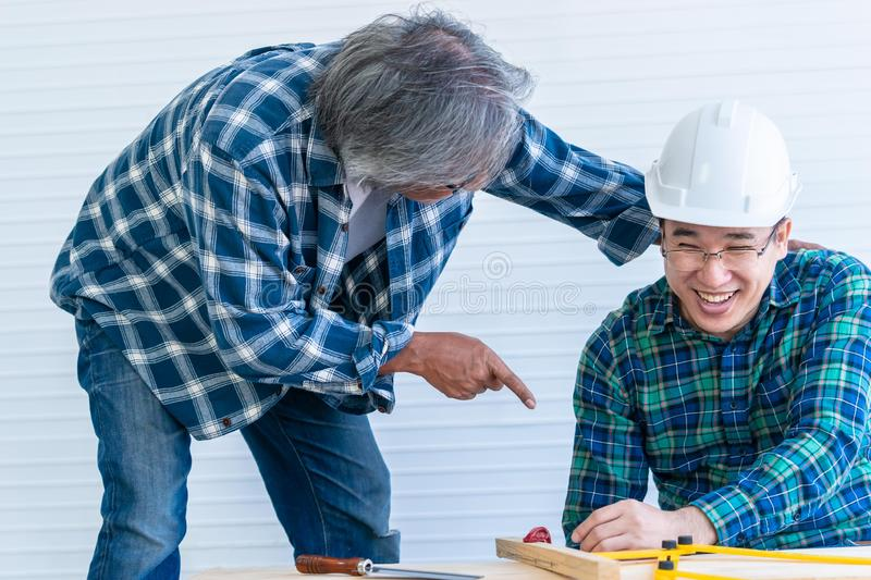 Senior builder bragging and helping a younger worker in home improvement project. Senior builder is bragging and helping a younger worker in home improvement royalty free stock photo