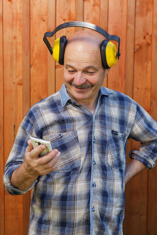 Senior builder in protective headphones holding hands in phone and reading message. Construction worker in protective headphones reading a message on phone royalty free stock photos